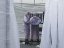 Medical staff wearing protective suits check documents as they wait for people with suspected symptoms of the new coronavirus, at a testing facility in Seoul, South Korea, Wednesday, March 4, 2020.
