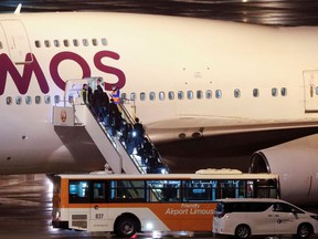 People board a plane chartered for British passengers after they left the coronavirus-hit cruise ship Diamond Princess at Haneda Airport, Tokyo Japan February 22, 2020.
