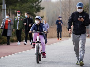 A young Chinese boy wearing a protective face mask as he rides at a park in Beijing on March 9, 2020 in Beijing, China.