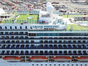 Passengers look out as the Grand Princess cruise ship docks at the Port of Oakland in Oakland, Calif., on March 9, 2020.