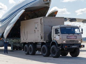 Russian servicemen load medical equipment and special disinfection vehicles into cargo planes while sending the supply to Italy at a military airdrome in Moscow March 22, 2020. (Russian Defence Ministry/Alexey Ereshko/Handout via REUTERS)