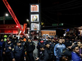 Police officers and onlookers stand outside the Tacubaya metro station, after several people were injured when two trains collided in the underground metro network, in Mexico City, Mexico, on March 11, 2020.