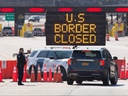In this file photo, U.S. Customs officers speaks with people in a car beside a sign saying that the U.S. border is closed at the U.S.-Canada border in Lansdowne, Ont., on March 22, 2020.