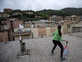 Vittoria Oliveri (front) plays tennis with Carola in background on rooftops of their house in Finale Ligure, Liguria Region, northwestern Italy on April 19, 2020, during the country's lockdown aimed at stopping the spread of the COVID-19 (new coronavirus) pandemic.
