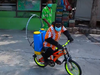 A chimp rides a bicycle sanitizing the facility at Samutprakarn Crocodile Farm and Zoo near Bangkok.