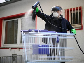 Working student Leon Rottmann coats a shopping trolley with a disinfectant at the mechanic's workshop of the Startup UVIS UV-Innovative Solutions in Cologne, Germany, on April 22, 2020.