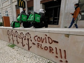 Uber Eats workers wait for orders as the spread of COVID-19 continues, in Lisbon, Portugal, April 25, 2020.