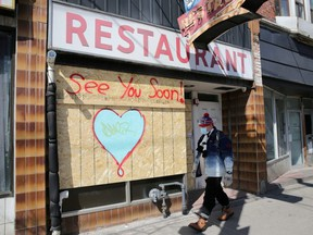 A man wearing a protective face mask passes a boarded up restaurant during the global outbreak of COVID-19 in Toronto, April 6, 2020.
