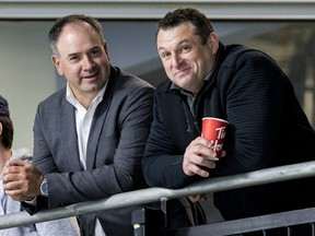 General manager Pierre Dorion (L) and head coach D.J. Smith watch their players at the Ottawa Senators development camp at the Bell Sensplex on June 27, 2019.