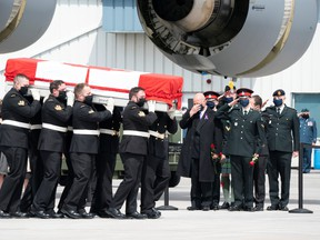 Family members look on as masked pallbearers carry the casket of Sub-Lt. Abbigail Cowbrough during a repatriation ceremony for the six Canadian Armed Forces members killed in a helicopter crash in the Mediterranean, at Canadian Forces Base Trenton, Ont., May 6, 2020.
