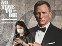 In this file photo taken on February 27, 2020 a woman wearing a facemask amid fears of the spread of the COVID-19 novel coronavirus walks past a poster for the new James Bond movie