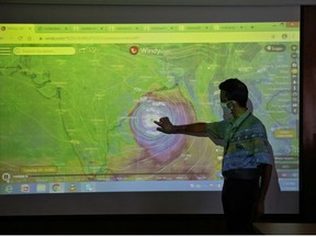 A scientist at India Meteorological Department Earth System Science Organisation, points to a section of the screen showing the position of the Cyclone Amphan to media people inside his office in Kolkata, India, May 19, 2020.