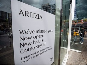 People wait to enter an Artizia clothing store on its first weekend open after a lengthy closure due to COVID-19, in Vancouver, on Sunday, May 17, 2020.
