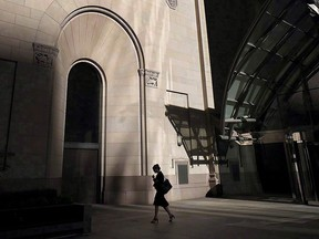 A woman walks through Toronto's financial district on July 30, 2018. With women bearing the brunt of the COVID-19 pandemic, federal officials are trying to figure out how recovery efforts can help get women back to work, earning more money and securing more stable jobs.