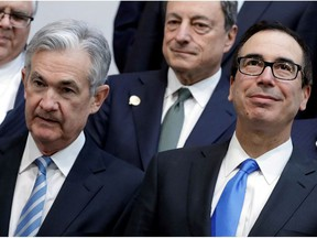 U.S. Treasury Secretary Steve Mnuchin (R) and Federal Reserve Chairman Jerome Powell pose for G-20 finance ministers and central banks governors family photo during the IMF/World Bank spring meeting in Washington, U.S., April 20, 2018.