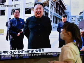 A woman walks past a television news screen showing a picture of North Korean leader Kim Jong Un attending a ceremony to mark the completion of Sunchon phosphatic fertiliser factory, at a railway station in Seoul on May 2, 2020.