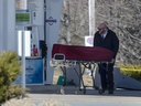 A worker with the medical examiner's office removes the body of Gabriel Wortman from a gas bar in Enfield, N.S. on Sunday, April 19, 2020.