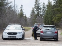 An RCMP officer talks with a local resident before escorting them home at a roadblock in Portapique, N.S., April 22, 2020.