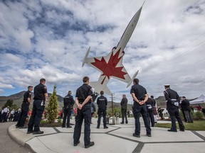 Kamloops firefighters stand during a minute of silence during a tribute ceremony to honour Capt. Jennifer Casey at the Kamloops Airport Thursday May 21, 2020.