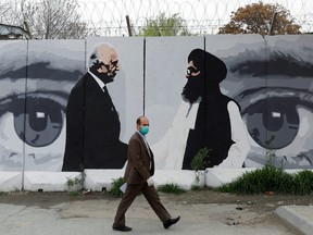 An Afghan man wearing a face mask walks past a wall painted with photo of Zalmay Khalilzad, U.S. envoy for peace in Afghanistan, and Mullah Abdul Ghani Baradar, the leader of the Taliban delegation, in Kabul, Afghanistan April 13, 2020.