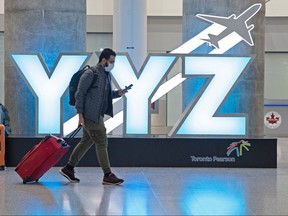A traveller passes a YYZ airport code sign in the international arrival lounge amid a growing global number of coronavirus cases at Pearson Airport in Toronto, March 13, 2020.
