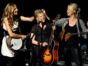 The Dixie Chicks' Emily Robison, left, and Martie Maguire, right, joke with Natalie Maines during their performance at the opening night of the Nokia Theatre L.A. Live in Los Angeles, Oct. 18, 2007.