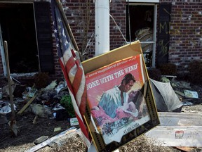 """A movie poster for """"Gone with the Wind"""" sits in a front yard of a home damaged by Hurricane Katrina in Chalmette, Louisiana, in St. Bernard Parish September 28, 2005."""