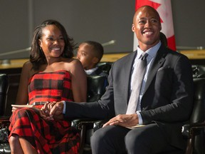 Henry Burris holds his wife Nicole Burris' hand during a ceremony in which he was awarded the Key to the City by Mayor Jim Watson. The local hero loves Ottawa, but he remembers a troubling experience at the Ottawa airport when he and his family returned from a trip to the Dominican Republic.