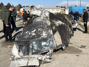 This file photo taken on January 11, 2020 shows people analysing the remains of the Ukraine International Airlines plane that crashed outside Tehran on January 8, 2020.
