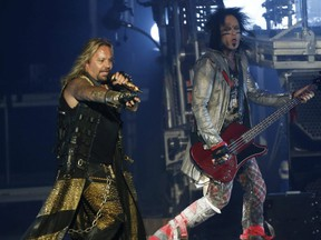 Motley Crue lead singer Vince Neil points to the crowd as he runs past bassist Nikki Sixx (right) during a concert at the Molson Amphitheatre in Toronto, Aug. 11, 2014.