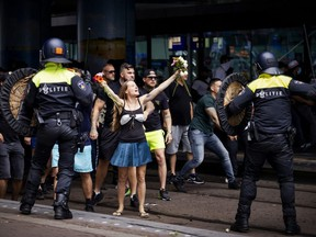 A woman reacts towards police at The Hague's Central Station as people gather at the Malieveld grounds to demonstrate against the Dutch government's handling of the COVID-19 pandemic, on Sunday, June 21, 2020.