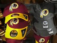 """Washington Redskins hats sit for sale at a sporting goods store on July 7, 2020 in Washington, DC. After receiving recent pressure from sponsors and retailers, the NFL franchise is considering a name change to replace Redskins. The term """"redskin"""" is a dictionary-defined racial slur for Native Americans."""