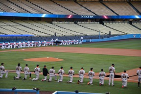 Players from the Los Angeles Dodgers and the San Francisco Giants take a knee during the national anthem at Dodger Stadium.