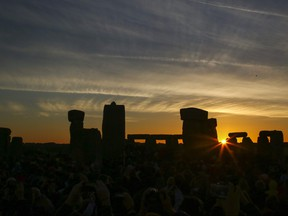 In this file photo revellers watch the sunrise as they celebrate the pagan festival of Summer Solstice at Stonehenge in Wiltshire, southern England on June 21, 2018.