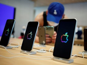 A man takes pictures of iPhones in the new Apple flagship store on its opening day following an outbreak of the coronavirus disease (COVID-19) in Sanlitun in Beijing, China, July 17, 2020.