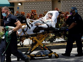 Emergency Medical Technicians leave with a patient at Hialeah Hospital where COVID-19 patients are treated, in Hialeah, Fla., Wednesday, July 29, 2020.