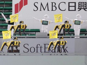 SoftBank Corp's humanoid robots Pepper and Boston Dynamics' robots SPOT in baseball uniforms cheer the team next to empty seats at a game between SoftBank Hawks and Tohoku Rakuten Golden Eagles in Fukuoka, Japan in this photo taken by Kyodo July 7, 2020.
