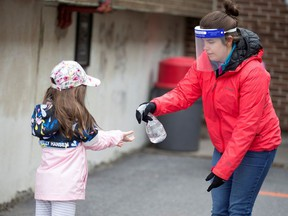 A student has her hands sanitized in the schoolyard, as schools outside the greater Montreal region begin to reopen their doors amid the coronavirus disease (COVID-19) outbreak, in Saint-Jean-sur-Richelieu, Quebec, Canada May 11, 2020.