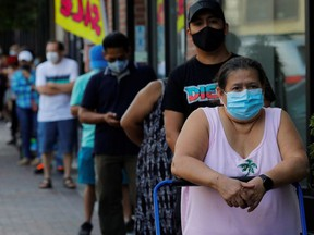 People wait in line for free groceries distributed by the Chelsea Collaborative in a city hard hit by the coronavirus disease (COVID-19) outbreak, in Chelsea, Massachusetts, U.S., July 22, 2020.   REUTERS/Brian Snyder ORG XMIT: PPP-BKS03