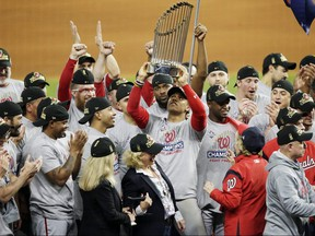 Juan Soto of the Washington Nationals hoists the Commissioners Trophy after defeating the Houston Astros to win the 2019 World Series at Minute Maid Park on October 30, 2019 in Houston.