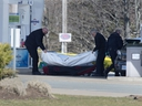 Workers with the medical examiner's office remove a body from a gas bar in Enfield, N.S. on April 19, 2020.