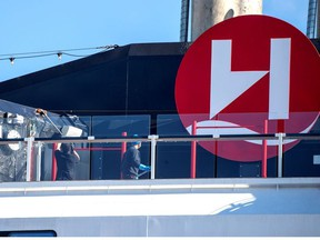People clean the MS Roald Amundsen ship, operated by Norway's Hurtigruten line, after its crew members were diagnosed with the coronavirus disease, at a port in Tromso, Norway, Saturday, Aug. 2, 2020.