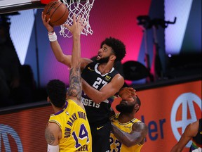 Jamal Murray, centre, of the Nuggets drives to the basket against Lakers defenders Danny Green (14) and LeBron James (23) during the second quarter in Game 4 of the Western Conference Finals during the 2020 NBA Playoffs at AdventHealth Arena at the ESPN Wide World Of Sports Complex in Lake Buena Vista, Fla., Thursday, Sept. 24, 2020.