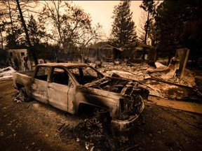 A burned vehicle is seen next next to a house reduced to ashes by the Glass Fire in Napa Valley, Calif, Monday, Sept. 28, 2020.