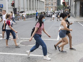 People wear face masks as they cross a street in Montreal, Sunday, August 9, 2020, as the COVID-19 pandemic continues in Canada and around the world. Government and public health officials need to empower people in their 20s to reduce the risk of contracting COVID-19, instead of blaming and shaming them for disproportionately representing new infections across the country, say experts.