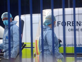 Forensic specialists are seen at the custody centre where a British police officer was shot dead in Croydon, south London, England, Friday, Sept. 25, 2020.