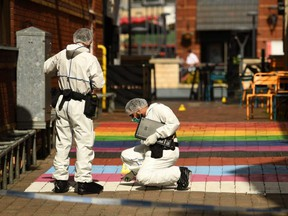"""Police forensics officers gather evidence on Hurst Walk, inside a cordon at Hurst Street, following a major stabbing incident in the centre of Birmingham, central England, on September 6, 2020. - One man was killed and two people were critically injured during a """"random"""" stabbing attack lasting several hours in Britain's second city of Birmingham, police said on Sunday. Detectives said they were hunting one suspect after being called to reports of stabbings at four separate locations in the city centre between 12:30 am (2330 GMT Saturday) and 2:30 am. (Photo by Oli SCARFF / AFP) (Photo by OLI SCARFF/"""