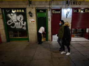 A couple walk past an closing a bar at the end of a day's work at Plaza Mayor in Madrid on October 24, 2020.