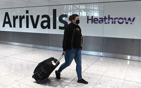 In this file photo taken on July 10, 2020, a passenger wearing a face mask or covering due to the COVID-19 pandemic, arrive at Heathrow airport, west London.