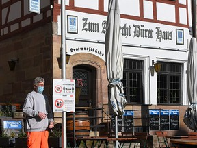 An employee of the city sets up an information board on measures regarding the novel coronavirus in front of a restaurant in the city of Nuremberg, Germany, on October 28, 2020.